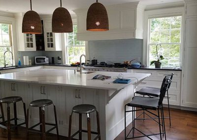 a kitchen with newly painted white cabinets
