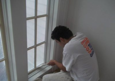 a man painting a window