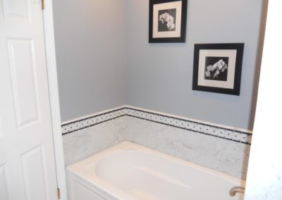 Bathtub and two pictures hanging on the wall