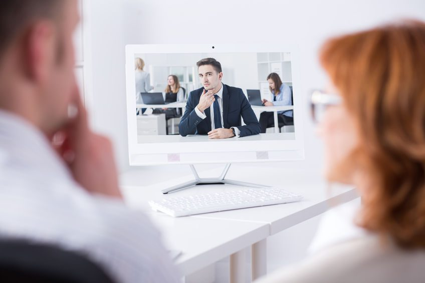 man and woman back view talking via video chat with young man in suit